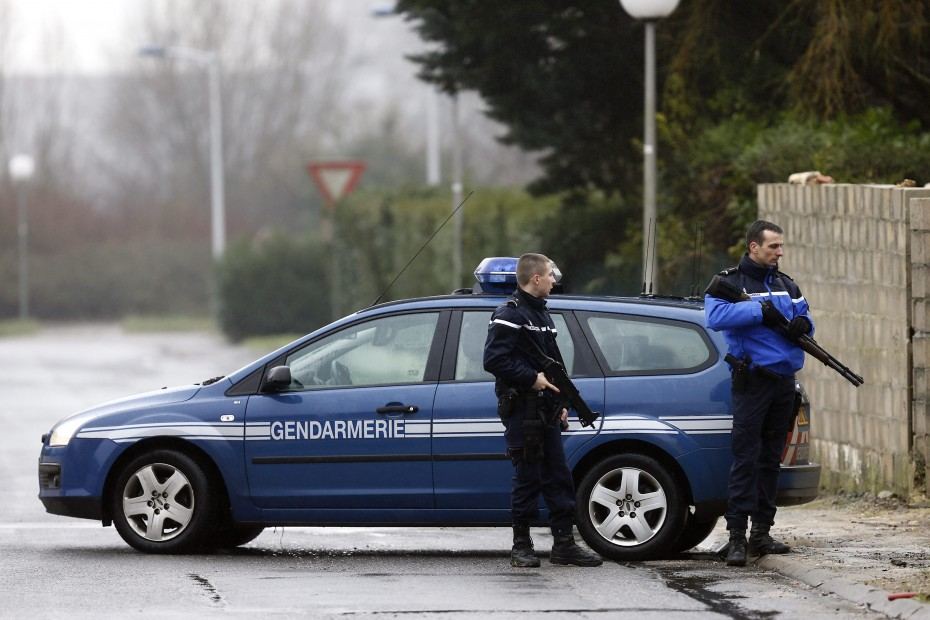 Police officers creating a security zone around the industrial area in Dammartin-en-Goele, where the two suspects are currently holding at least one hostage. -- Photo by EPA