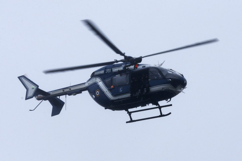 A helicopter flying over the building where the suspects are. -- Photo by EPA