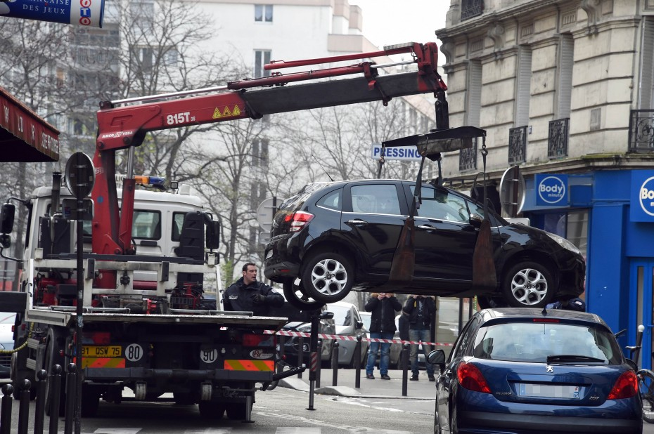 This picture, which was taken yesterday, shows a truck towing the car believed to have been used as the escape vehicle by three gunmen who attacked the office of French satirical newspaper, Charlie Hebdo. - Photo by AFP.