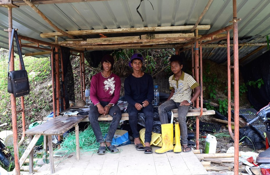 During their break,  (from left) Zofian and his co-workers Atiaz and Ramli rest under a shed.