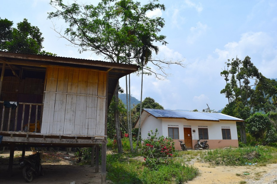The orang asli prefer to live in their own homes (left) despite government's efforts of building brick houses for them.