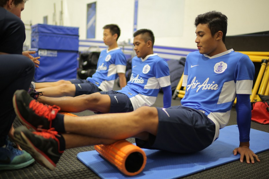 Like all football players, the boys did some strength and conditioning activities during their warm up sessions. Here, they are using the foam rollers to relieve and restore their calf muscles. Photo: AirAsia