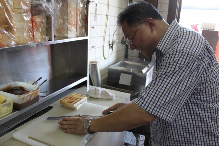 David demonstrates how the workers at Restoran Hua Mui toast bread on a charcoal grill.