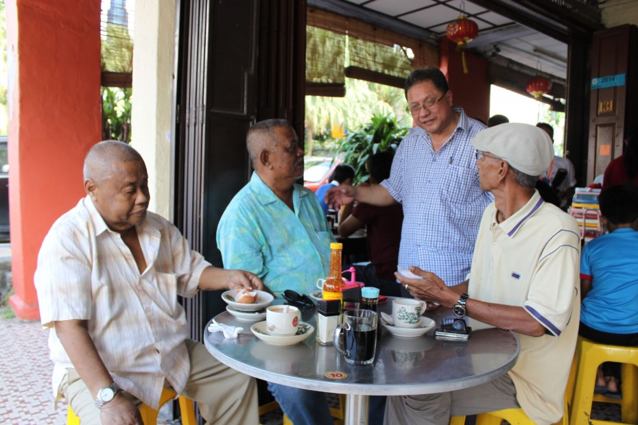 David (standing) often chats with his regulars. Ali Wahab, 58, (left) has been going to Restoran Hua Mui for over 40 years and likes that it has kept its old-school kopitiam look.