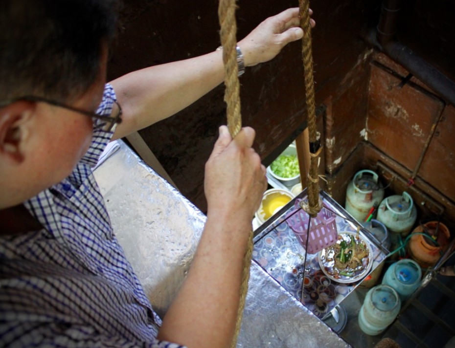 David Chiang demonstrates how the workers at Restoran Hua Mui use the pulley system to bring food up from the kitchen to the second floor.According to David, this system has been around since day one.