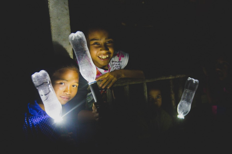 The children of Kampung Lemoi are all smiles as they stand next to their brand new solar powered water bottle lamps. Kampung Lemoi had long been plunged in darkness, and villagers resorted to old-fashioned light sources like bonfires to get some light. - Photo: Joe Kiat