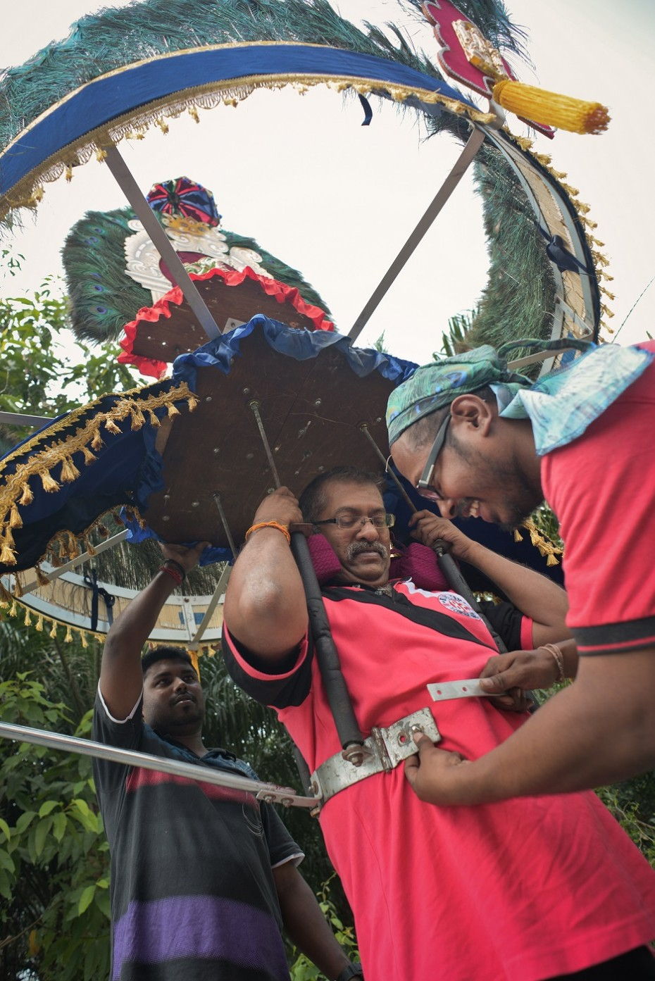 Kavadi maker and porter Bala (right) helping a client test the weight and fitting of a kavadi. — Photo: ELROI YEE/The Star