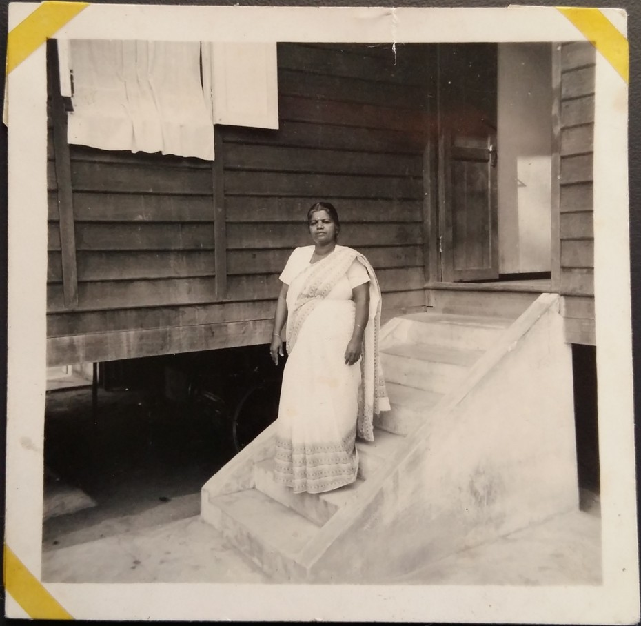 Pushparani's mother standing at the staircase outside their home.