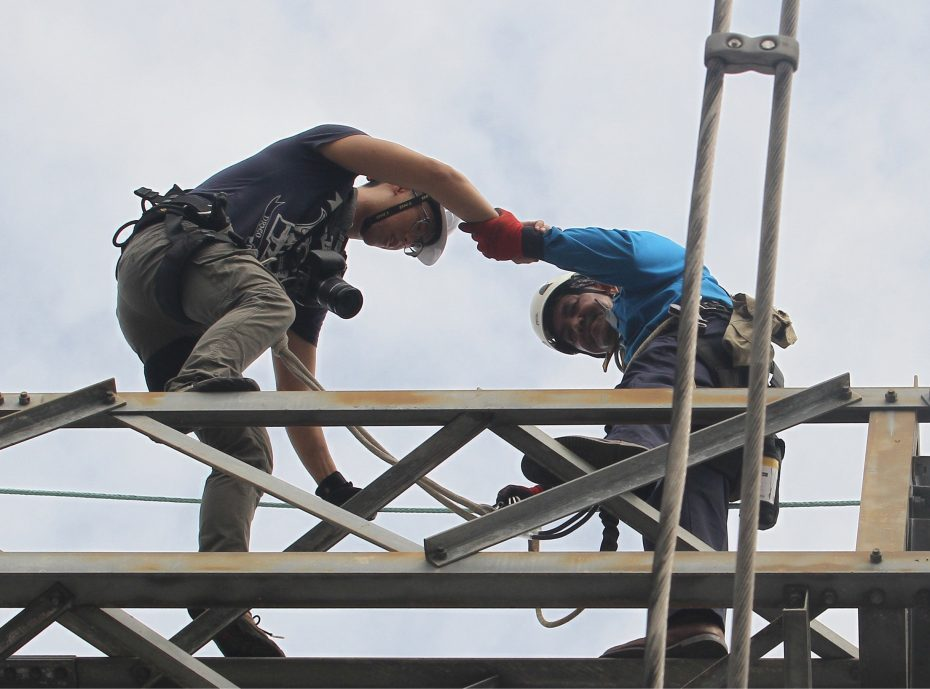 Cheng (left) on top of a 10m electric pylon, while covering a story about TNB repairmen. — SAIHAN GHANI/The Star